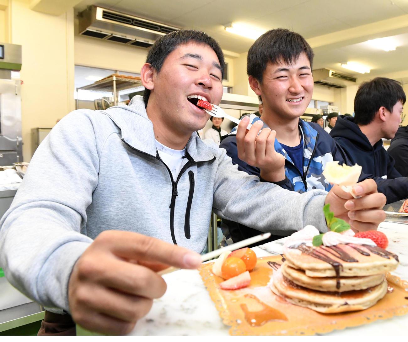 九州パンケーキ作りに挑戦したオリックスの新人選手。宮城(左)は紅林から食べさせてもらう(撮影・前岡正明)