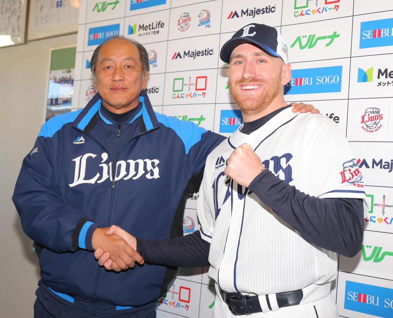 西武入団会見で渡辺GMと笑顔で握手を交わすギャレット(撮影・河田真司)