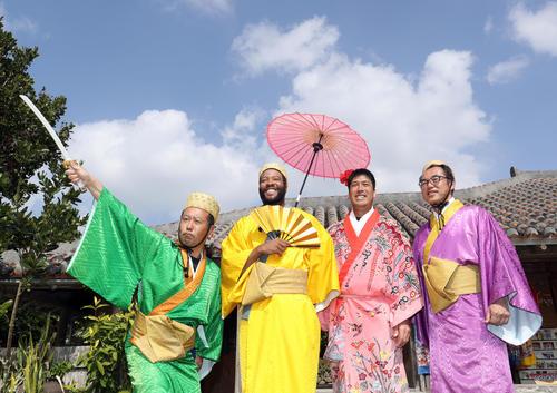 休日に「石垣やいま村」を訪れ王族の衣装を着込み広報通訳と写真に納まるロッテのジャクソン(左から2人目)(撮影・垰建太)