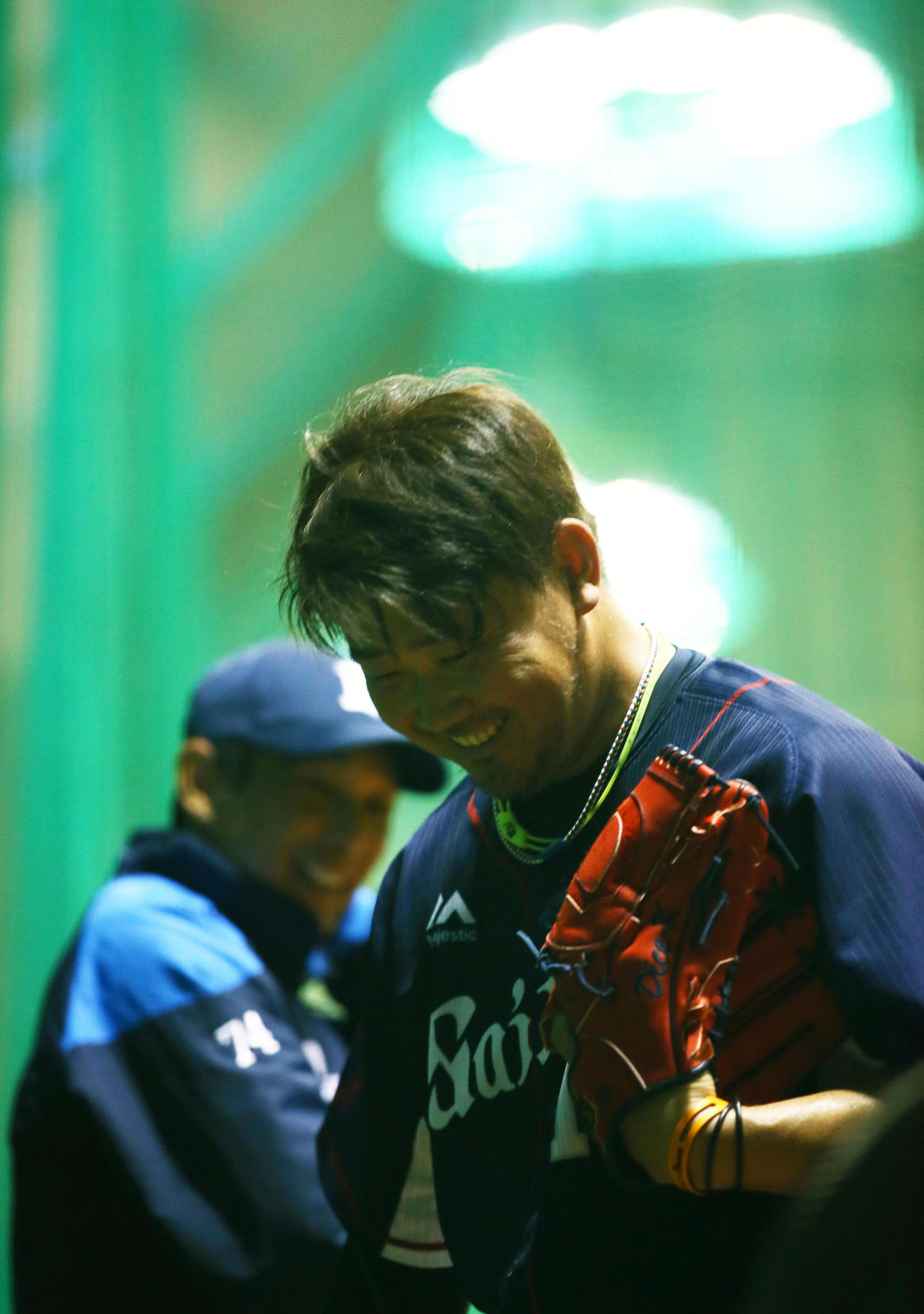 ブルペンでの投球を終えた西武松坂(右)は西口コーチ(左)の声に笑顔を見せる(撮影・足立雅史)