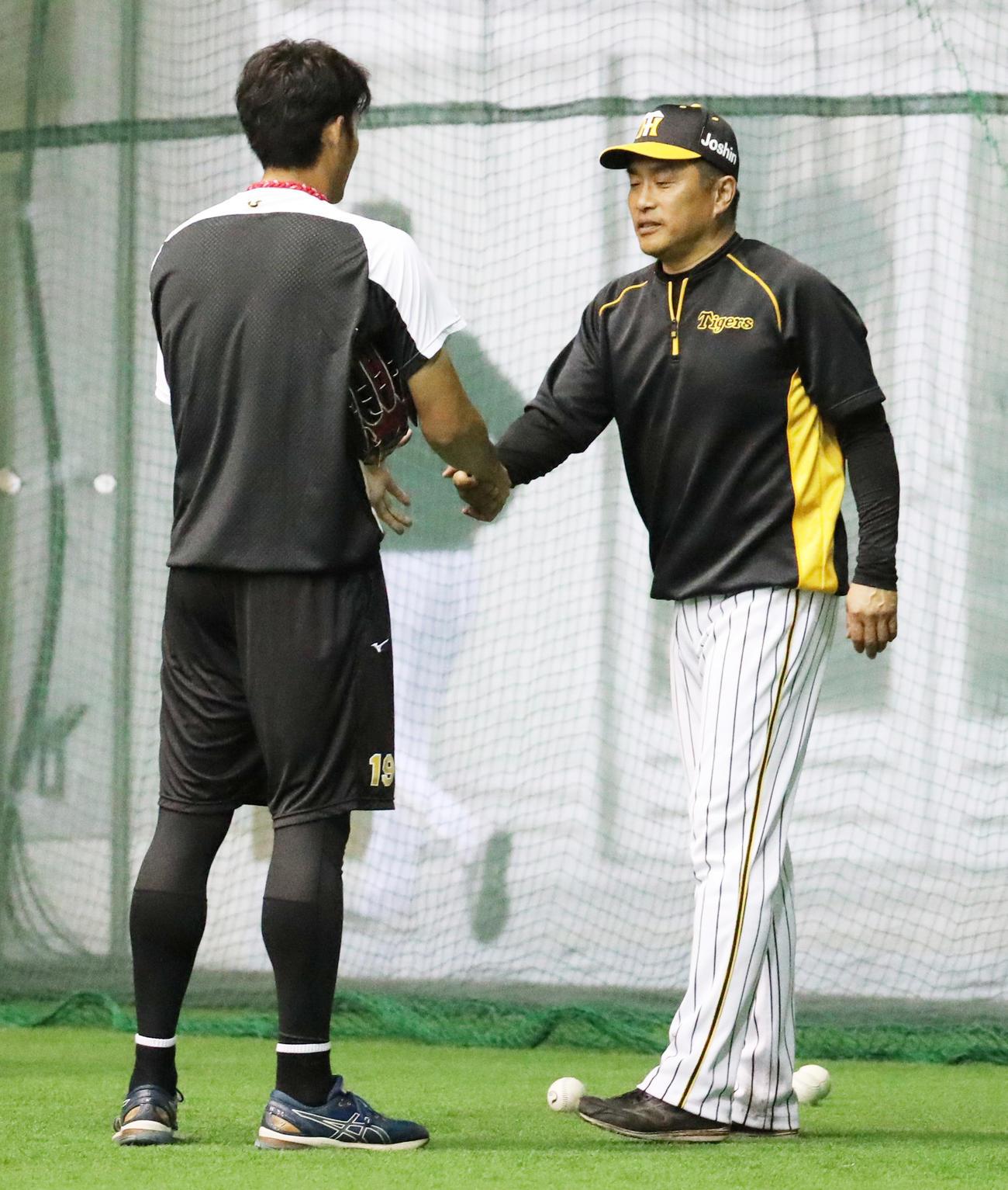 藤浪晋太郎(左)に最後の指導を行い握手を交わす山本昌臨時投手コーチ(撮影・清水貴仁)