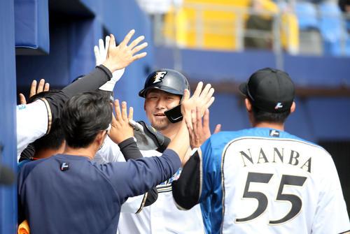 日本ハム対広島 4回裏日本ハム無死一塁、逆転となる右越え2点本塁打を放ちチームメートに出迎えられる中田(撮影・佐藤翔太)
