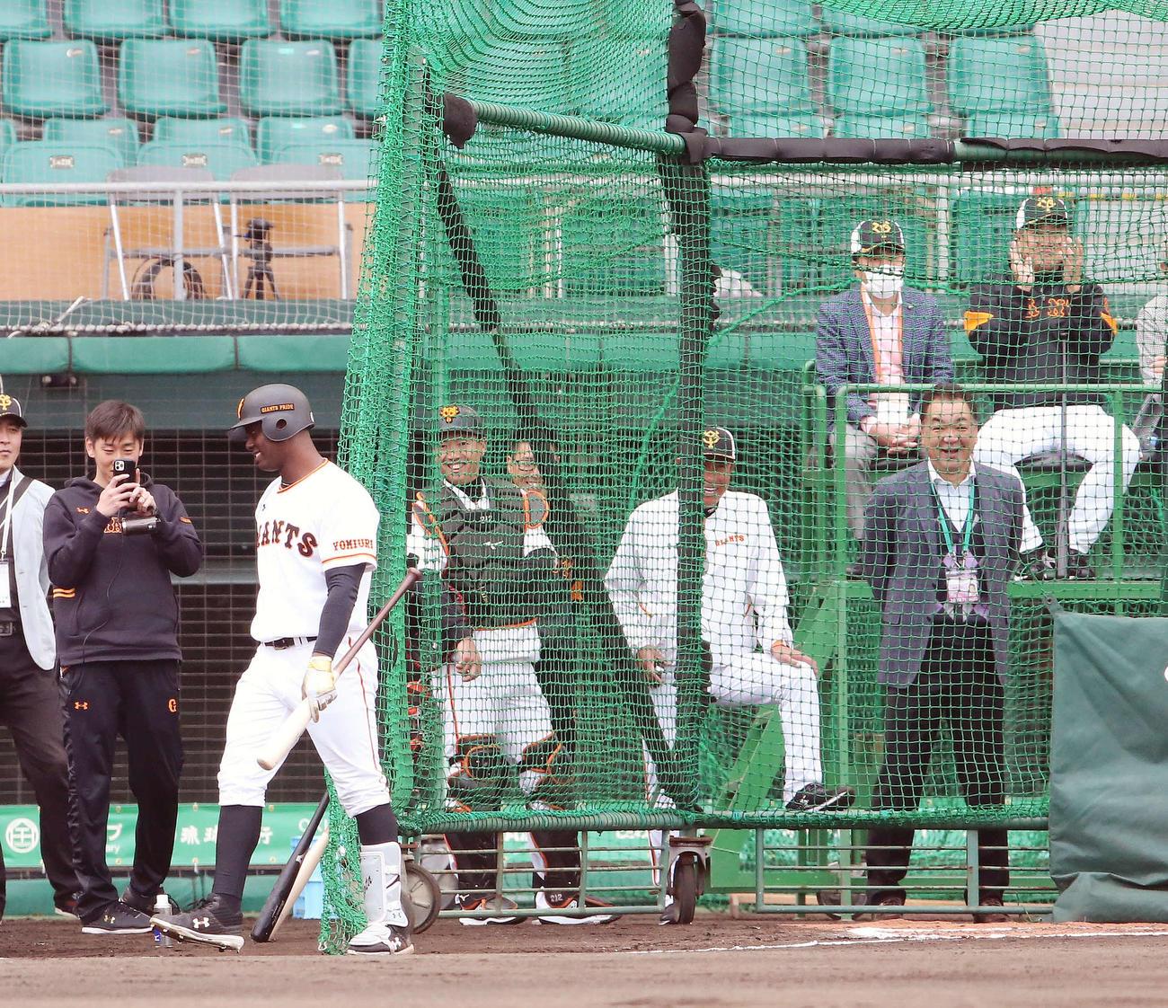 フリー打撃で巨人菅野から左中間に本塁打を放ったモタ(左手前)に拍手する原監督(後方右)(撮影・河野匠)