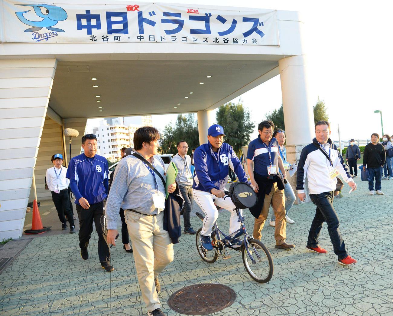 キャンプ地の北谷に戻り、約1時間の練習を行い記者に囲まれ自転車で引き揚げる与田監督(撮影・森本幸一)