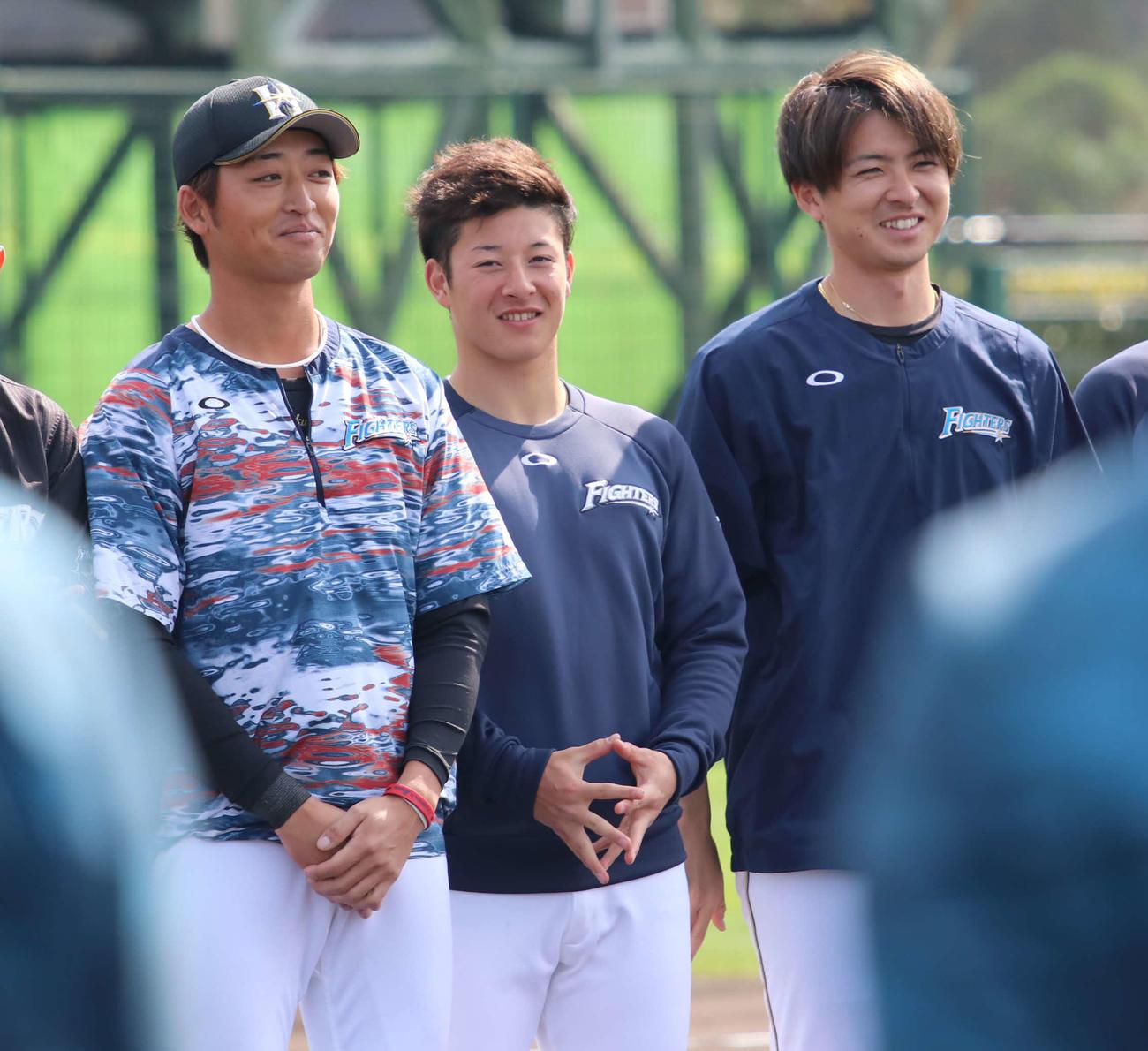 沖縄・国頭での2軍キャンプを打ち上げ、手締めに参加し笑顔を見せる日本ハム吉田輝(中央)。左は白村、右は上沢(撮影・山崎純一)
