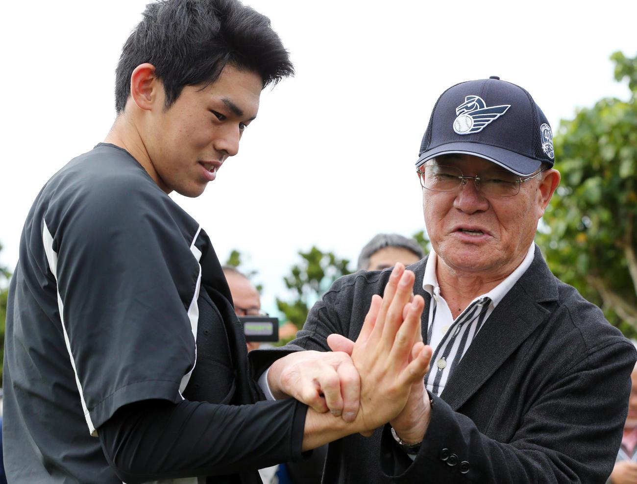 2月19日の練習中、ロッテ佐々木朗(左)は張本氏と手を合わせながら言葉を交わす(撮影・垰建太)