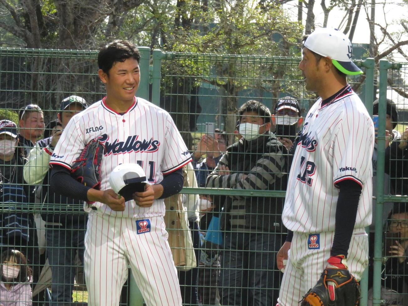 ブルペンで2度目の投球練習を終え、小山田ブルペン捕手と話すヤクルトのドラフト1位、奥川(左)