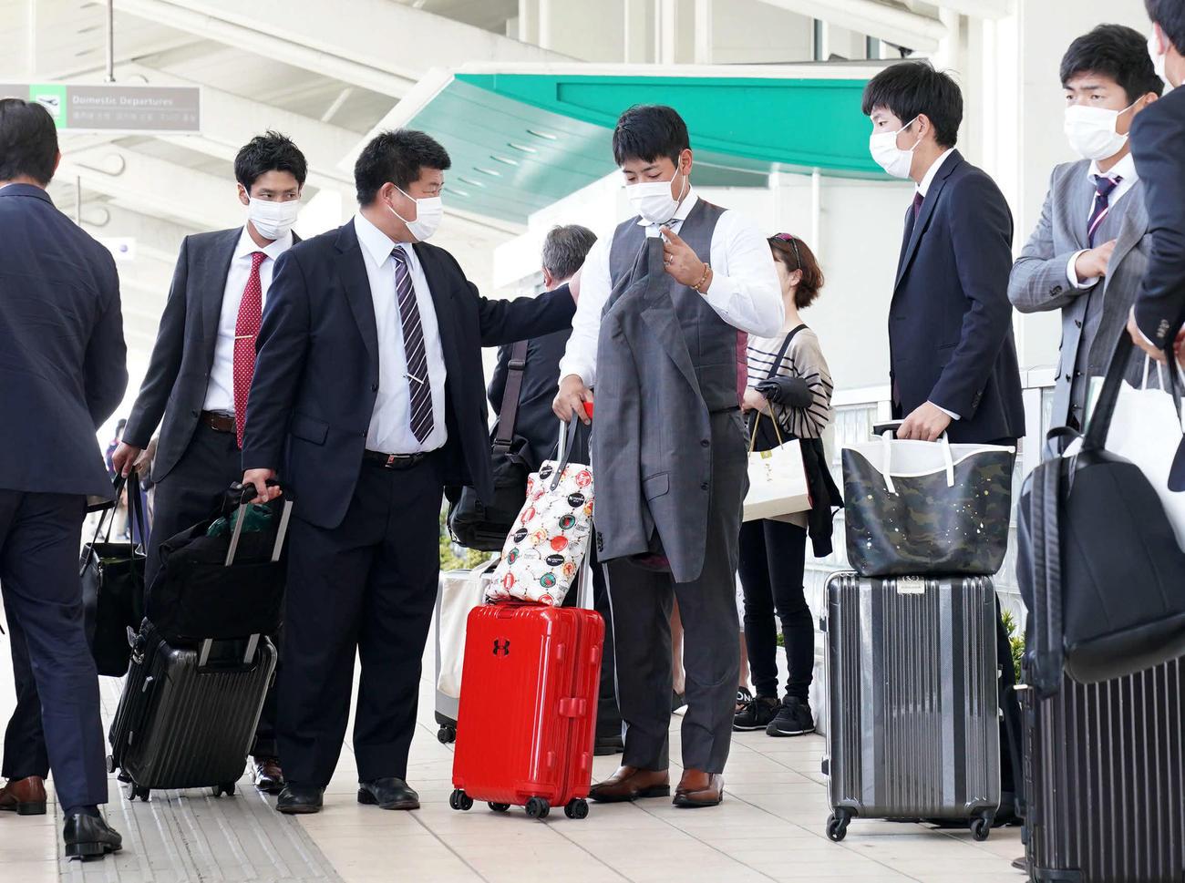 巨人沖縄キャンプを終え、那覇空港で通りがかりの人に声をかけられる岡本(中央)。空港では乗客のみならず、職員も含むほとんどの人がマスクを着用していた(撮影・加藤諒)