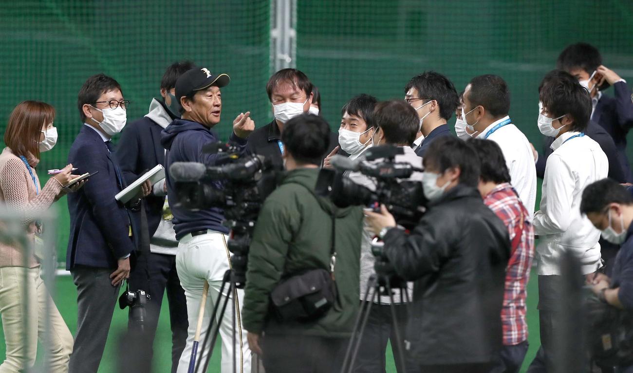 マスクをした報道陣に囲まれ取材を受ける日本ハム栗山監督(撮影・黒川智章)
