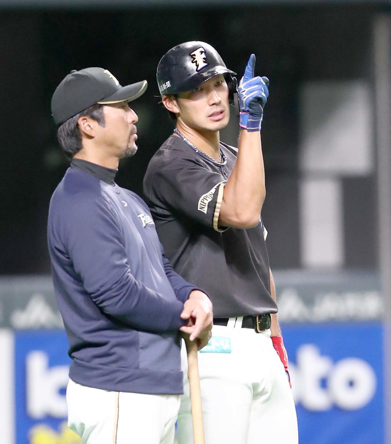 小笠原ヘッドコーチ(左)と話す日本ハム大田(撮影・黒川智章)