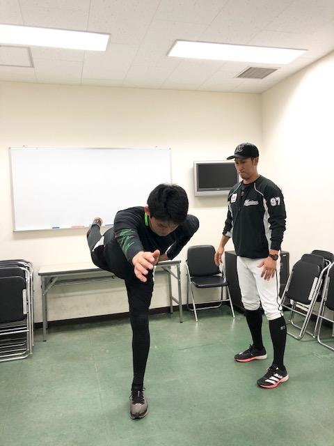 片足を後方に垂直に伸ばしバランスを取るロッテ佐々木朗(左)と菊地1軍ストレングスコーチ(球団提供)