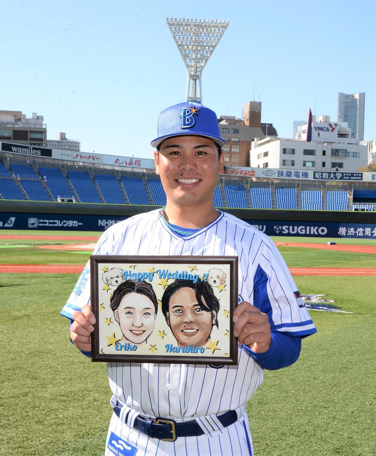 結婚を発表したDeNA浜口は妻恵理子さんと自身の似顔絵を手に笑顔を見せる(撮影・鈴木正章)