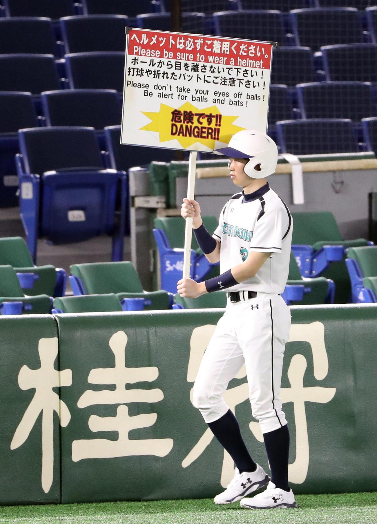 巨人対DeNA 8回表を終え、無観客にも関わらず、打球の注意喚起のボードを持ち歩くボールボーイ(撮影・狩俣裕三)