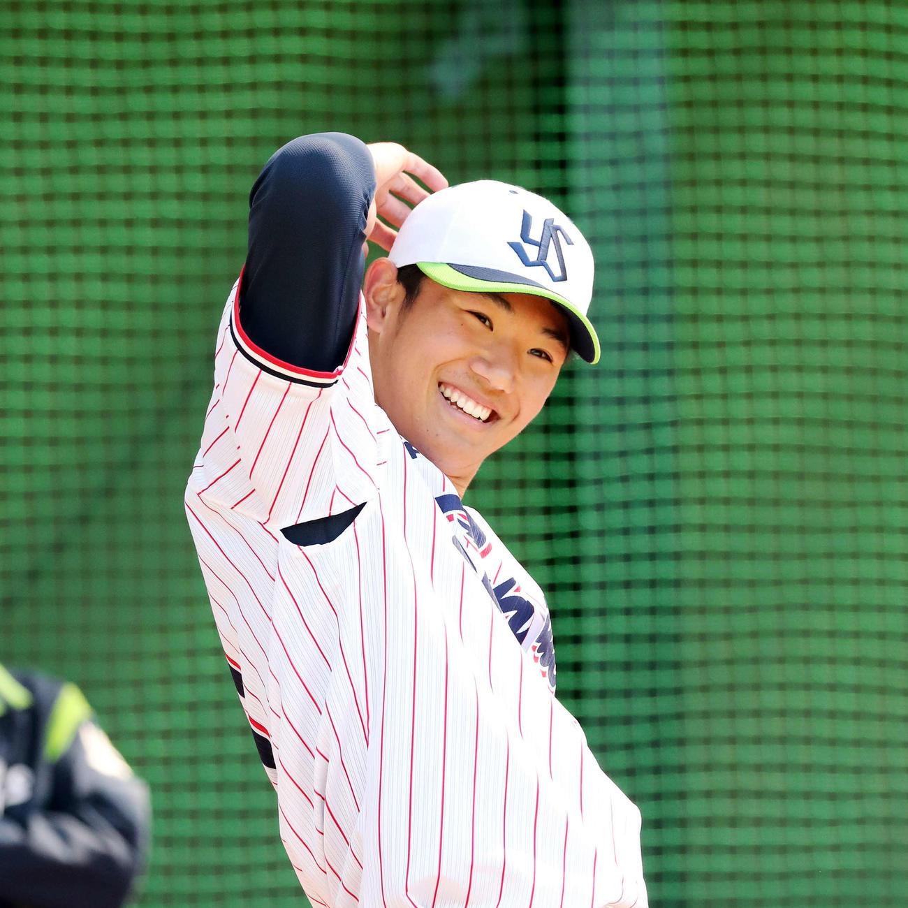 ブルペンで投球練習中、笑顔を見せるヤクルト奥川(撮影・鈴木正人)