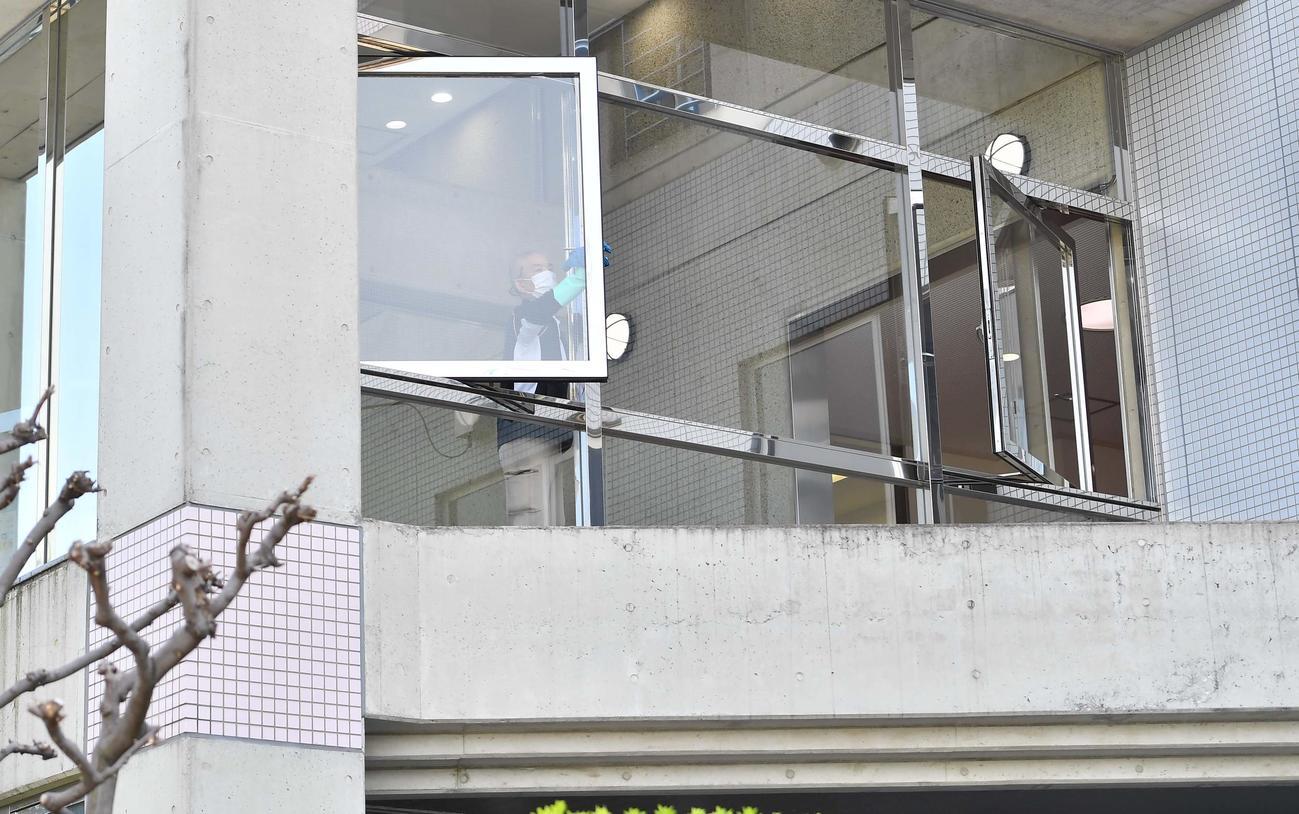 虎風荘の窓を拭くゴム手袋にマスク姿の関係者
