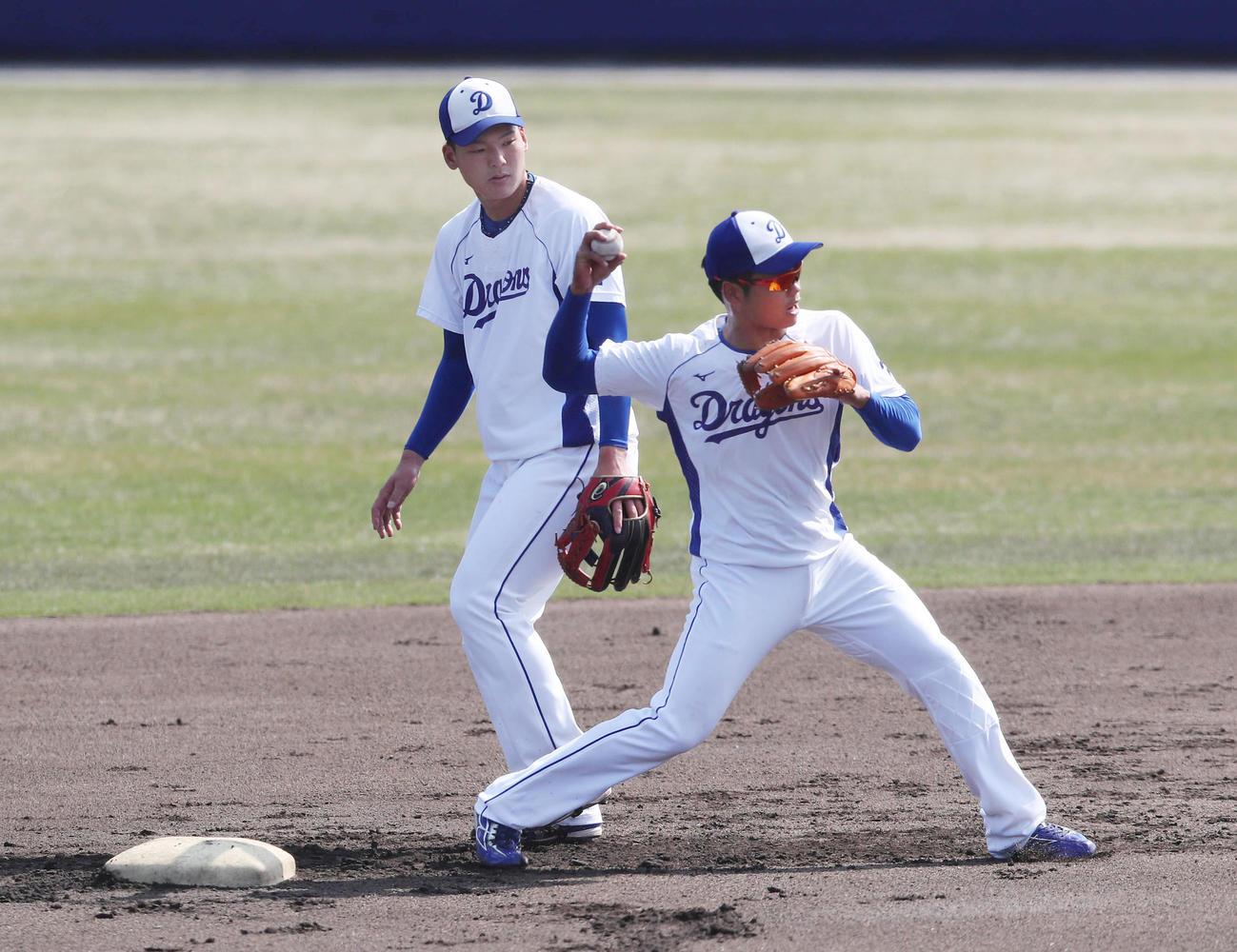 併殺打の守備練習をする石川昂(左)と根尾
