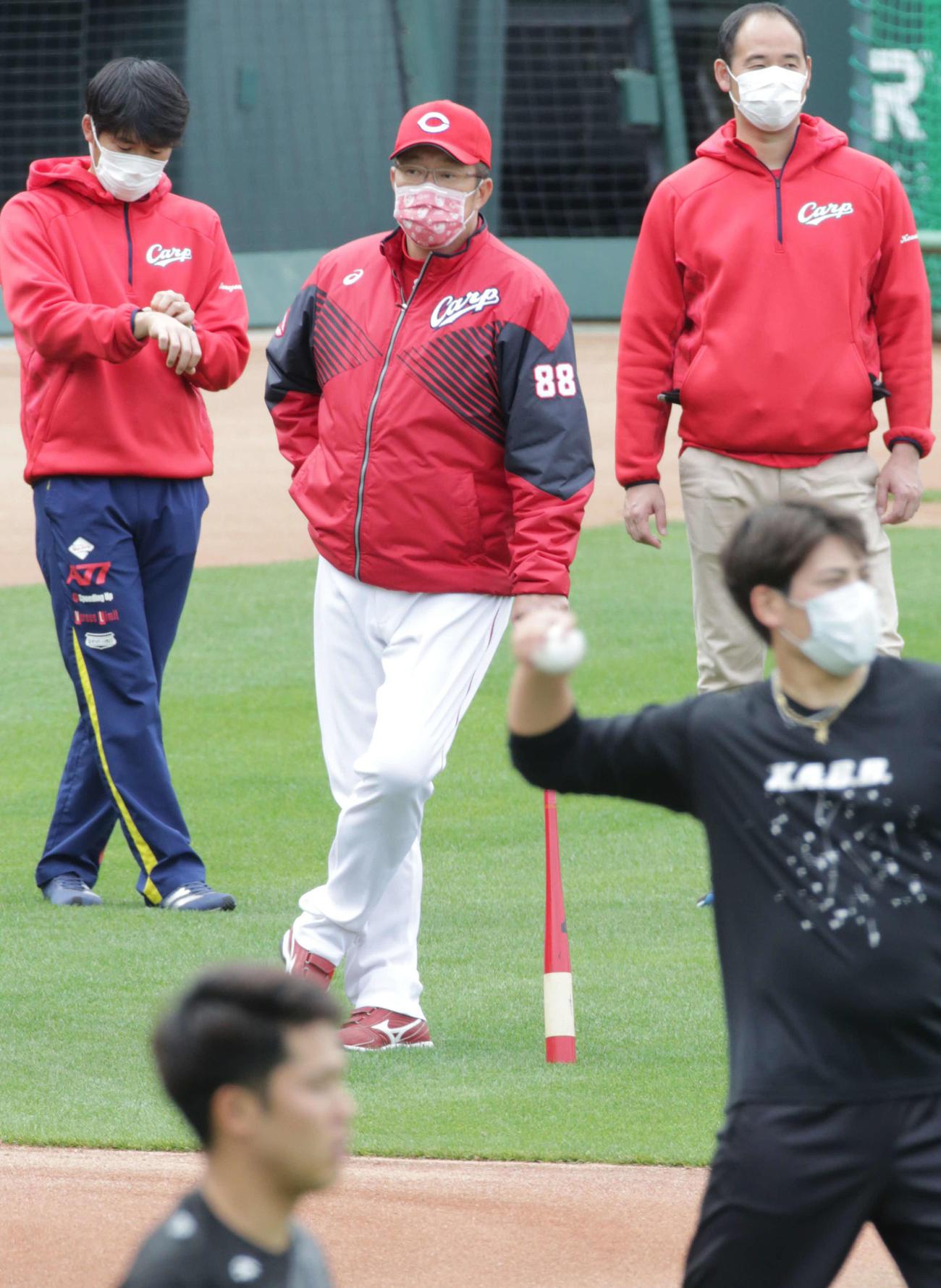 練習を見守る佐々岡真司監督。右手前のマスク姿は九里(撮影・加藤孝規)
