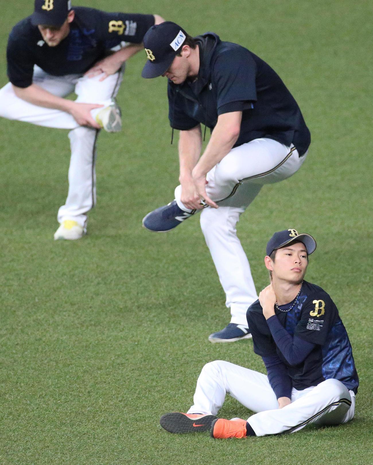 山岡(手前)は投手陣がストレッチする中、首を気にする(撮影・上山淳一)