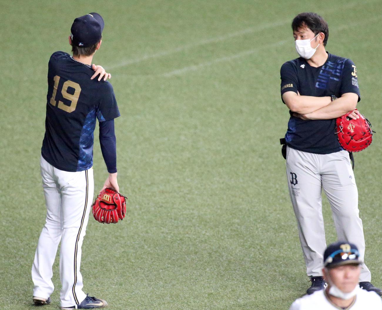 山岡(左)は、キャッチボールを中断し、右肩をさわる(撮影・上山淳一)