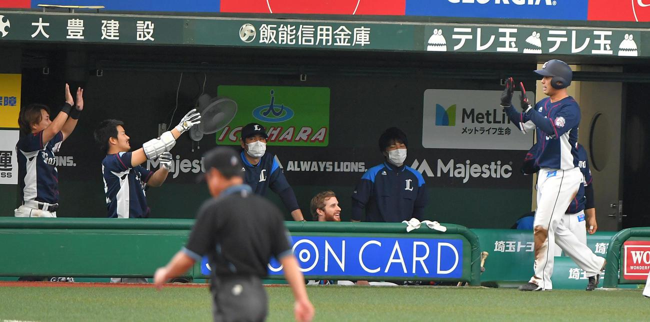 西武紅白戦 6回表2死二塁 打者・源田壮亮の適時三塁打で生還し、ベンチ前でエアータッチする紅組の柘植世那(右端)(代表撮影)