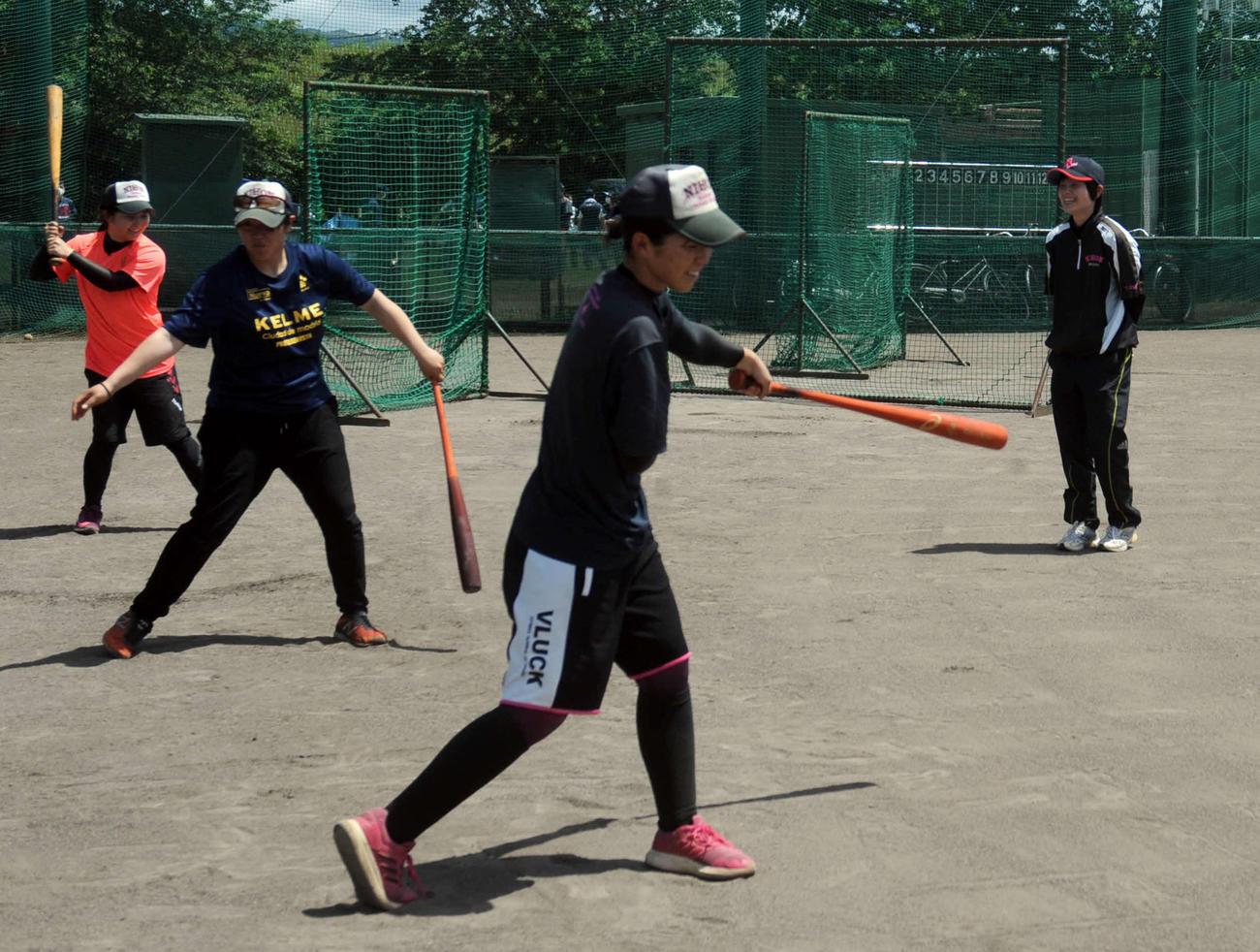 自主練習をする選手たちを見守る坪内監督(右奥)