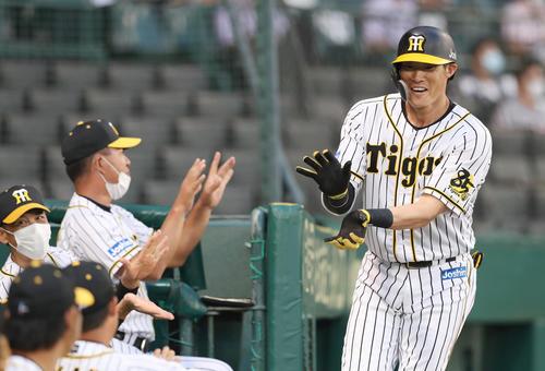 3回裏阪神2死一塁、左越え2点本塁打を放った糸井(右)はポーズを決めて矢野監督(左端)らに迎えられる(撮影・前田充)