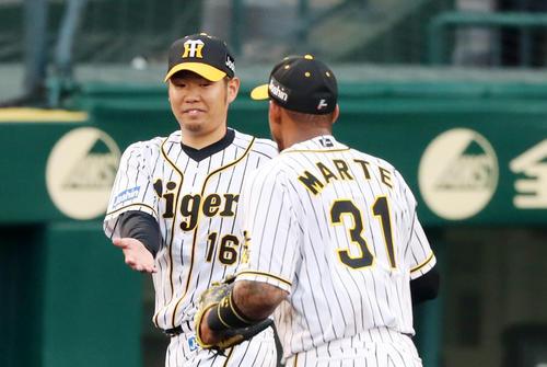 阪神対ソフトバンク 2回表、2度の好守備を見せたマルテ(右)を笑顔で迎える西勇(撮影・加藤哉)