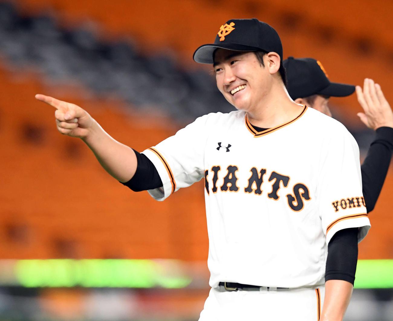 今季初完封勝利を飾った巨人菅野は、ナインの出迎えに笑顔で指をさす(撮影・たえ見朱実)
