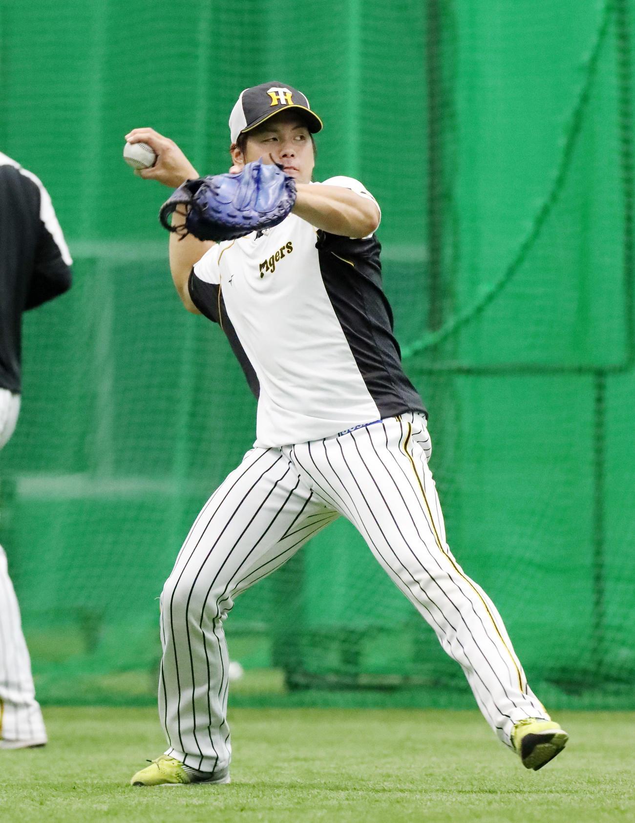 ノックを受ける梅野隆太郎はボールをスローイングする(撮影・加藤哉)