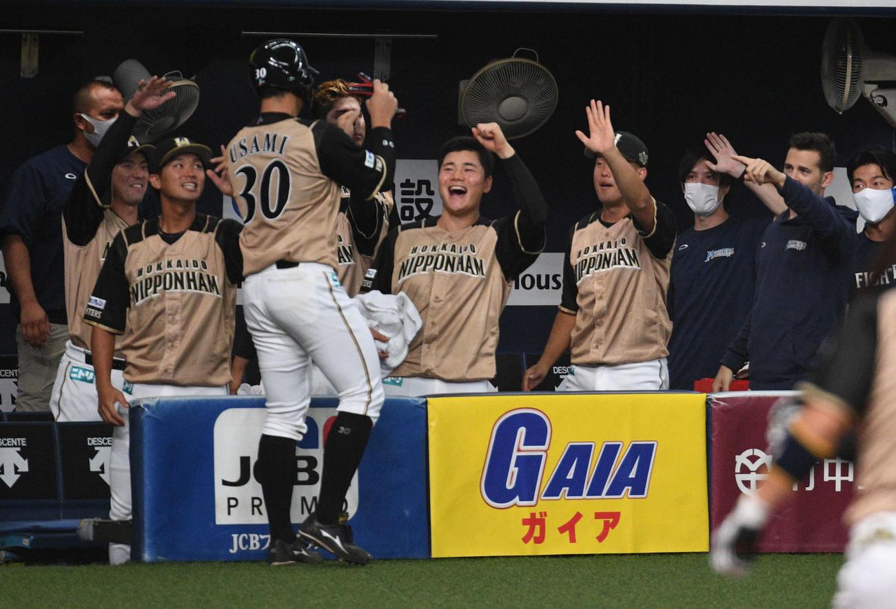 オリックス対日本ハム 2回表日本ハム2死満塁、大田泰示の適時打で生還しナインに迎えられる宇佐美塁大