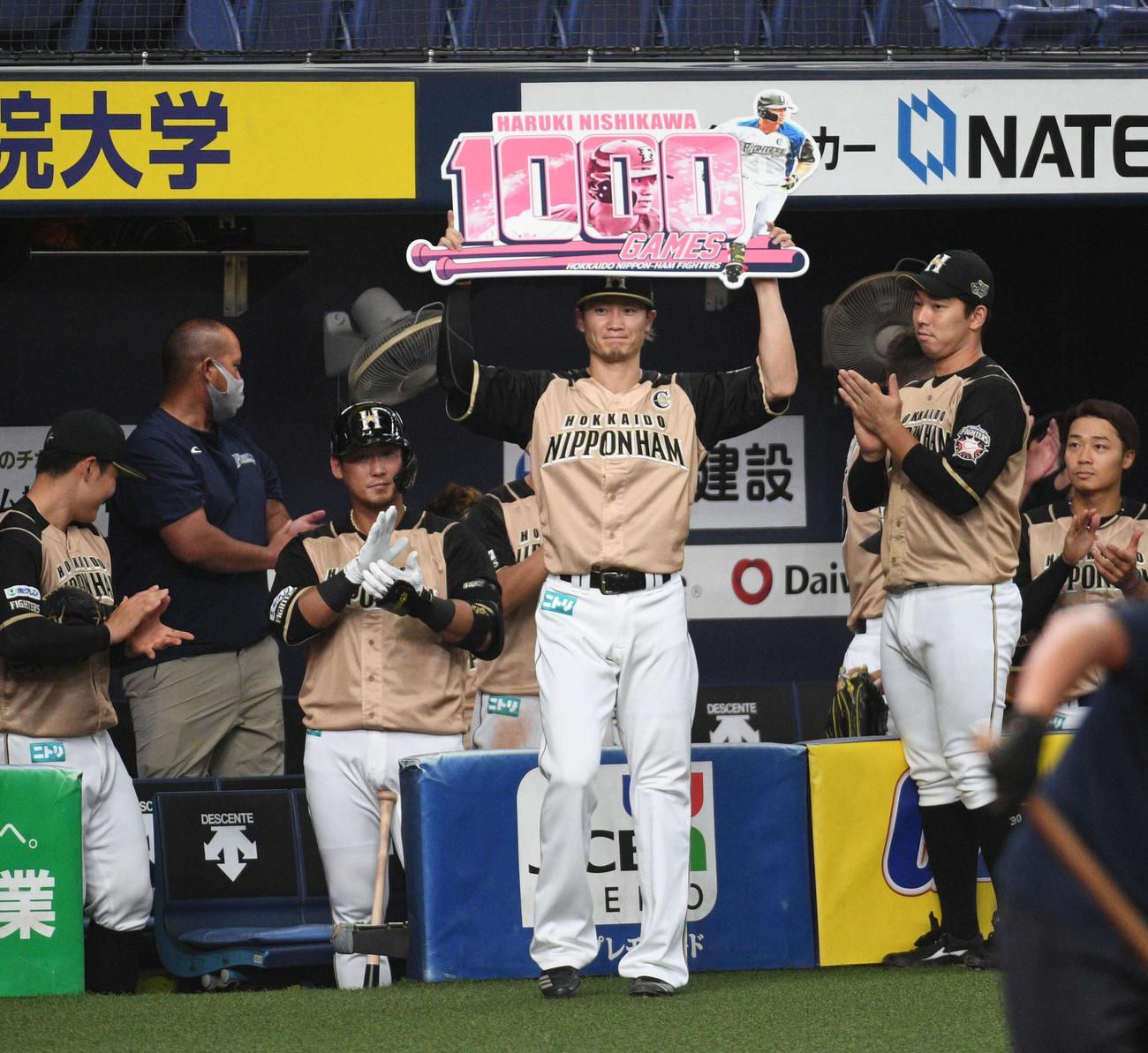 オリックス対日本ハム 1000試合出場を達成し、ボードを掲げる日本ハム西川(撮影・渦原淳)