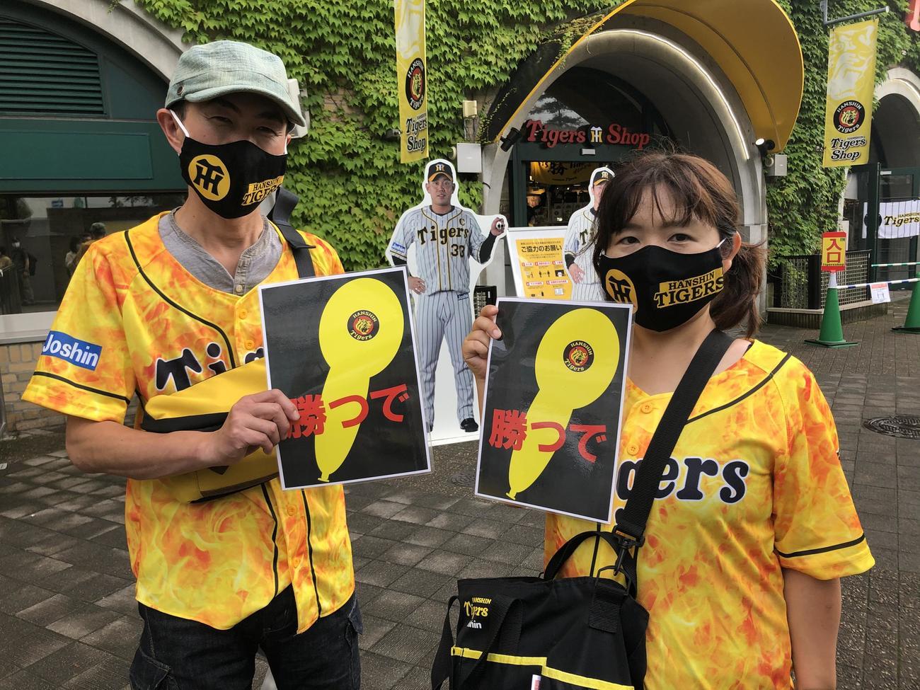 有観客試合初戦となった10日阪神-DeNA戦に訪れた曽我部始さん(左)と優子さんは、この日のために購入した阪神柄のマスクを着用し、ジェット風船の絵が描かれた手作りボードを持参した(撮影・磯綾乃)