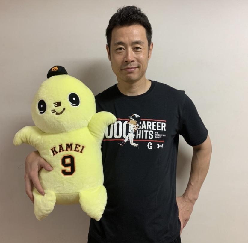 1000安打達成記念の「アンダーアーマーTシャツ」を着て、「ビッグぬいぐるみカメット」を手に笑顔の巨人亀井(球団提供)