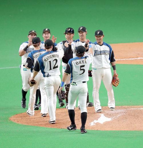 日本ハム対ロッテ 試合終了後、ナインを笑顔で出迎える日本ハム中田(右)(撮影・佐藤翔太)