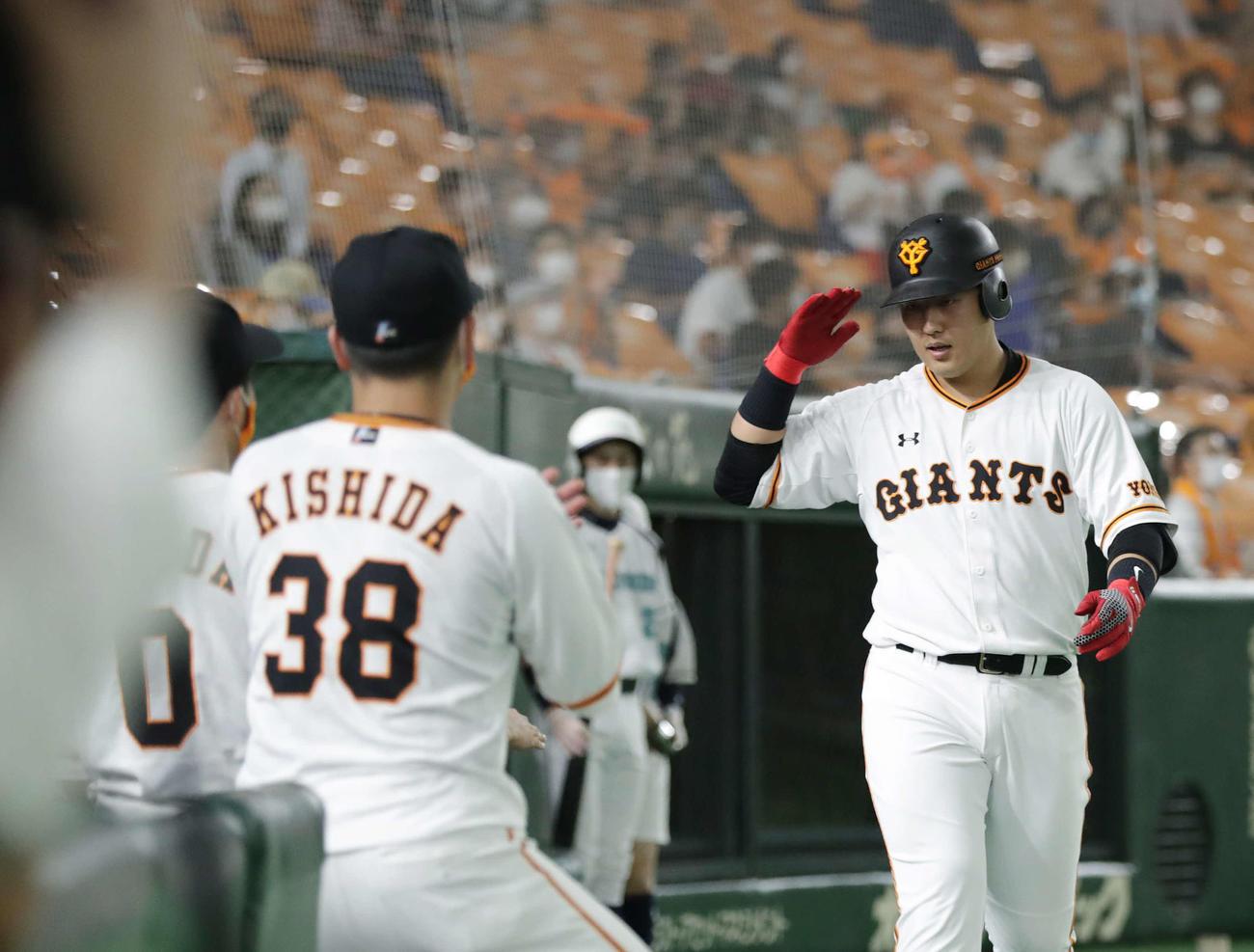 巨人対DeNA 4回裏巨人1死、左越え本塁打を放ちベンチ前で敬礼する岡本(撮影・河野匠)