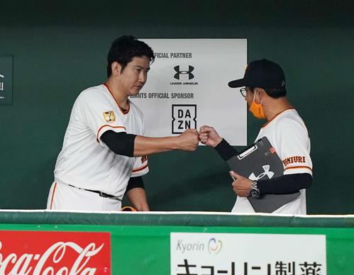 巨人対DeNA 7回表を投げ終え、宮本投手総合コーチ(右)とグータッチを交わす巨人菅野(撮影・鈴木みどり)
