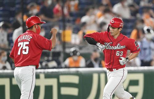 巨人対広島 4回表広島無死、先制の右越えソロ本塁打を放った西川(右)は広瀬コーチとエアタッチ(撮影・鈴木みどり)