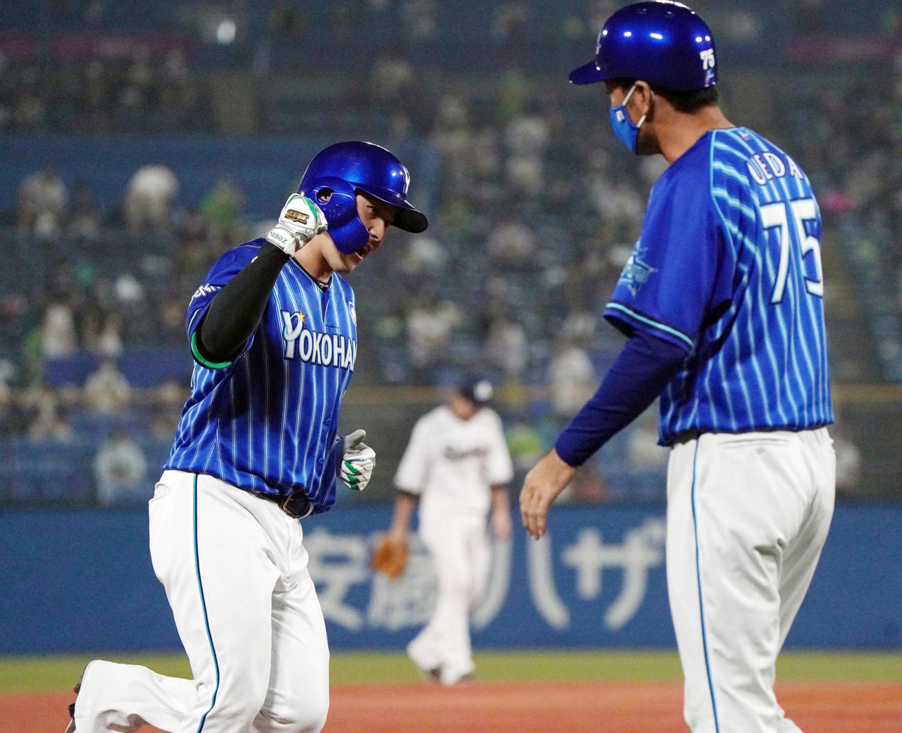 5回表DeNA2死二塁、本塁打を放ち上田コーチ(右)にガッツポーズをする佐野(撮影・狩俣裕三)