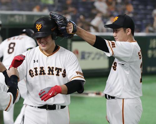 巨人対ヤクルト 6回裏巨人2死、左越え本塁打を放った岡本(左)は菅野に頭をはたかれる(撮影・河野匠)