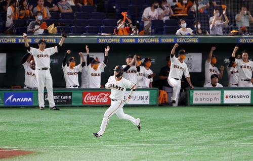 巨人対ヤクルト 2回裏巨人2死二塁、坂本は左翼2点本塁打を放ち、バンザイして喜ぶ菅野(左奥)ら喜ぶ巨人ベンチを背に一塁を回る(撮影・浅見桂子)