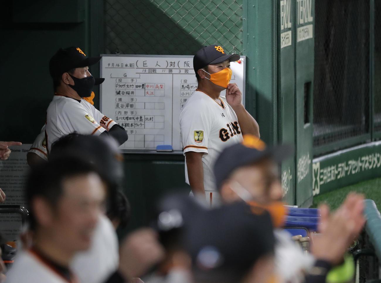 巨人対阪神 4回裏巨人1死二塁、立岡の適時打にベンチで笑顔の阿部ヘッドコーチ代行(右)。左は原監督(撮影・河野匠)