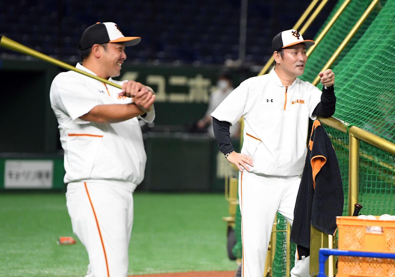 グラウンドに姿を見せた巨人元木ヘッドコーチは、阿部ヘッドコーチ代行と笑顔を見せる(撮影・たえ見朱実)