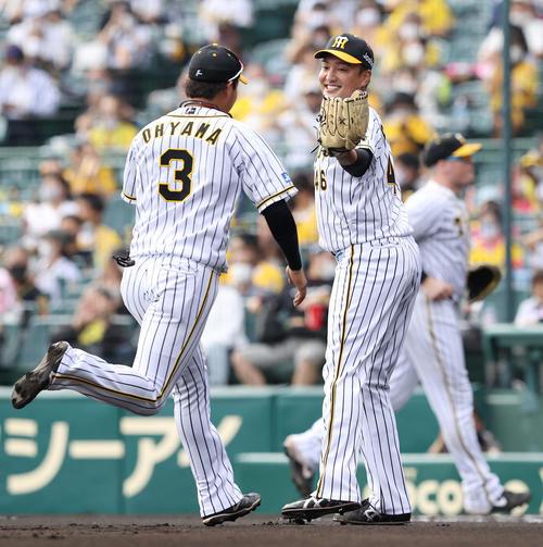 阪神大巨人1回表ジャイアンツ2社坂本の打球を好捕した大山(左)を笑顔で迎え秋山(撮影垰建太)