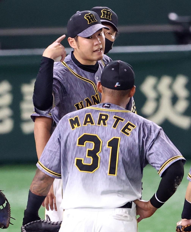 巨人対阪神 5回裏巨人無死一塁、エラーをしたマルテ(手前)とジェスチャーを交え話をする西勇(撮影・狩俣裕三)