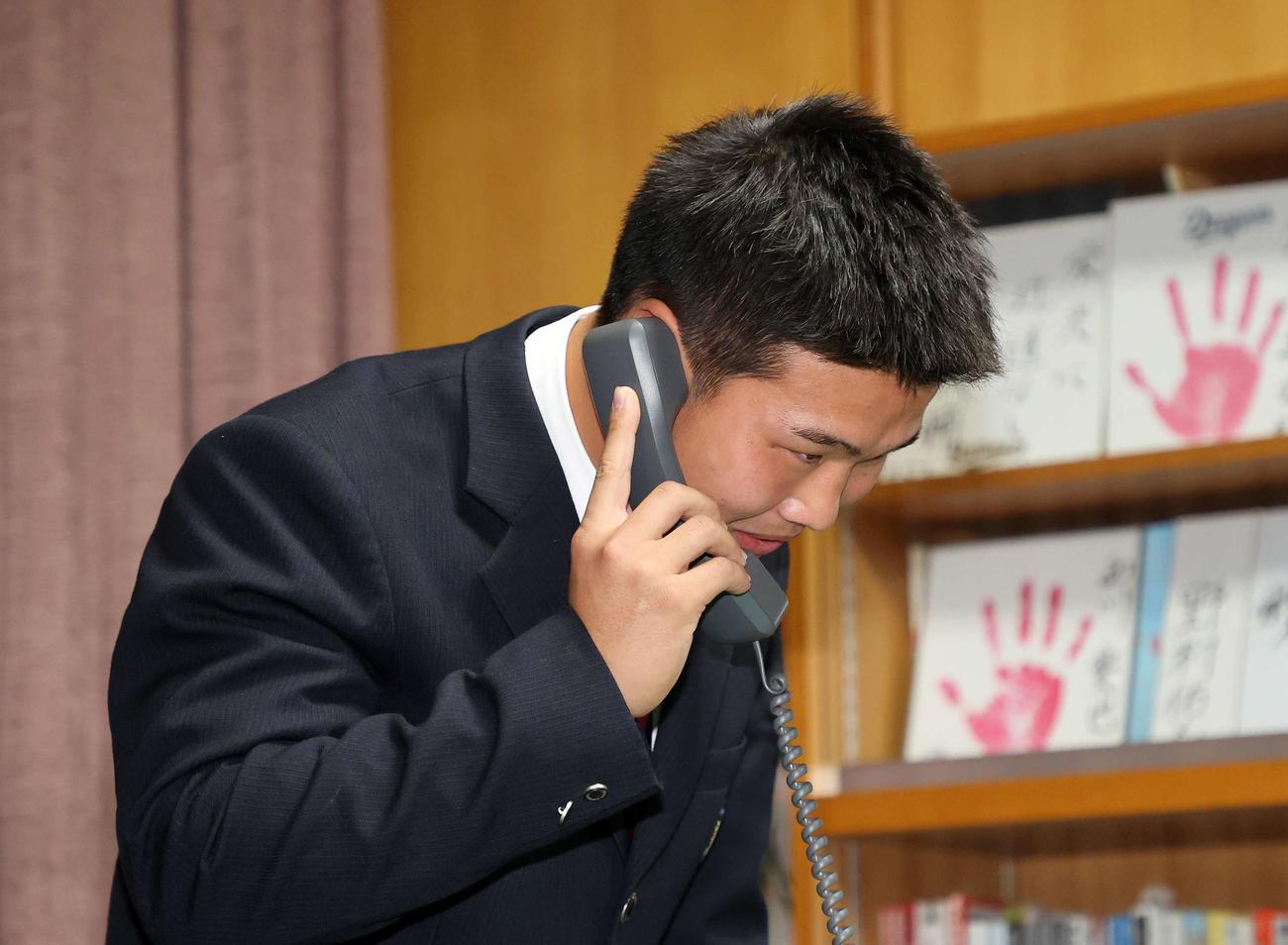 ソフトバンクに1位指名され父親に電話する花咲徳栄・井上(撮影・鈴木正人)