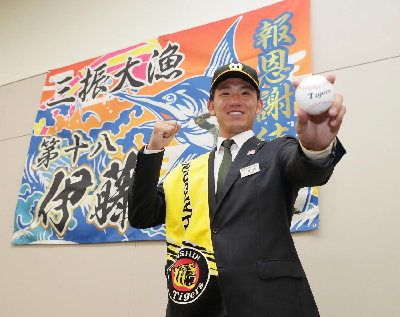 阪神から2位指名を受け、同僚から贈られた大漁旗の前で笑顔でポーズをとるJR東日本・伊藤(撮影・前田充)