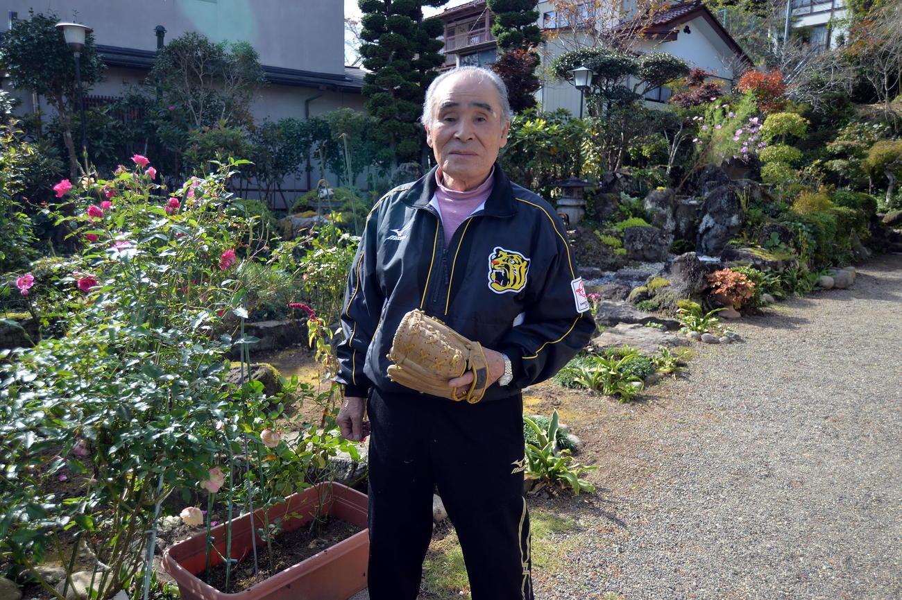 阪神ドラフト1位佐藤の父博信さんが小学校時代に愛用したグラブを手にする勲さん(撮影・中島正好)
