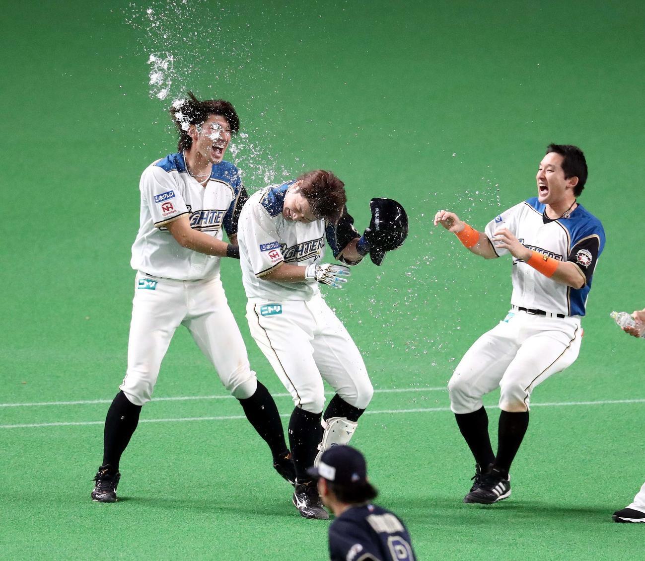 日本ハム対オリックス 10回裏、サヨナラ右犠飛を放った渡辺は大田らに水をかけられる(撮影・黒川智章)