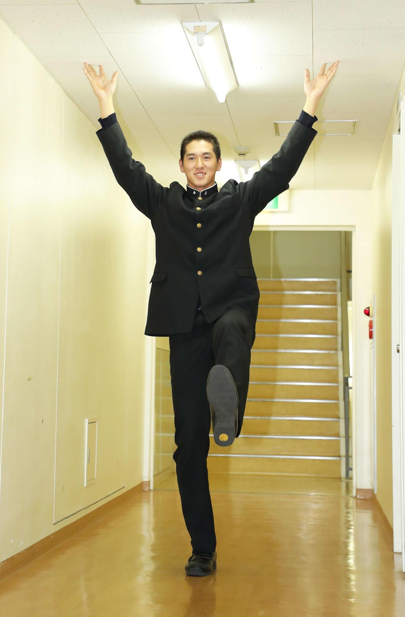高身長を生かしたポーズを廊下でとり写真に納まる、巨人ドラフト5位指名の二松学舎大付・秋広(撮影・河田真司)