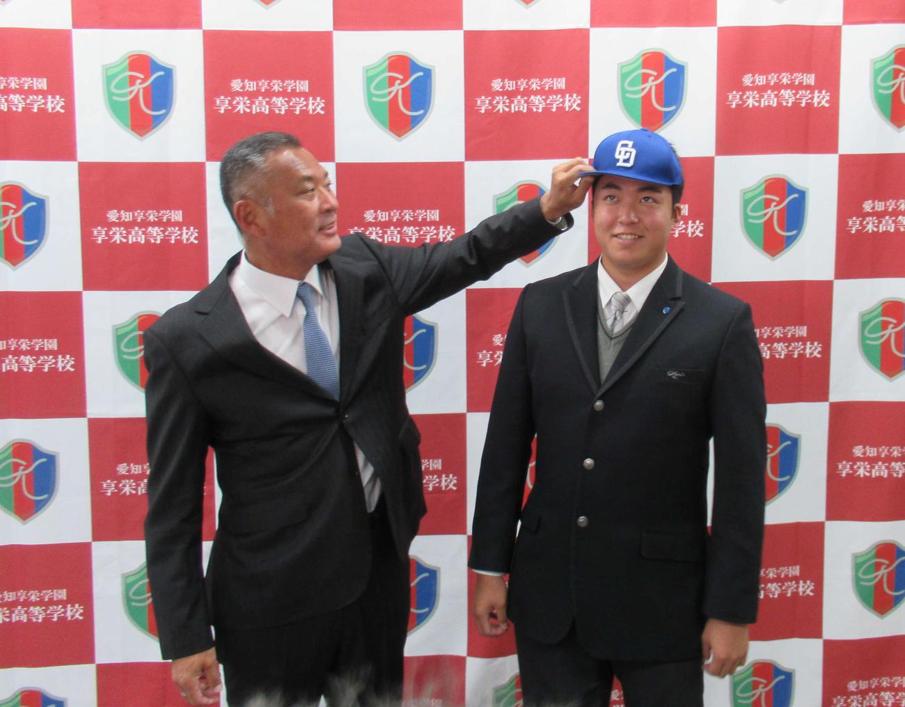 享栄の先輩でもある近藤スカウト(左)から帽子をかぶらせてもらう中日育成2位・上田洸太朗投手
